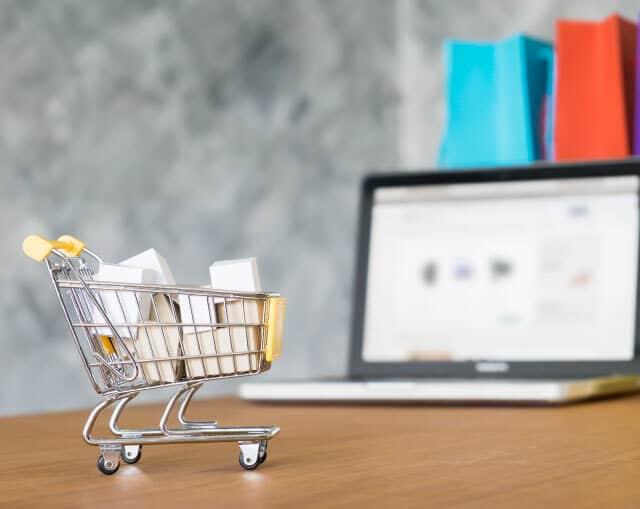 Kolica-sa-proizvodima-i-internet-prodavnica-otvorena-na-laptopu-u-pozadini